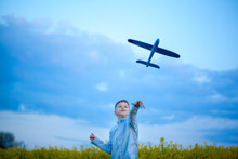 Boy Throwing Toy Airplane In Summer Day.