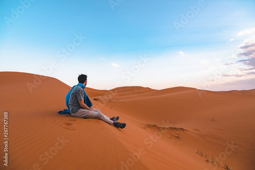 Fotografia  Young traveler man resting on a dune in the Sahara Desert