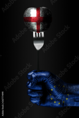 A hand with a drawn EU flag holds a fork, on which is a ball with a drawn England flag, a sign of influence, pressure, grip and anecxia Wallpaper Mural