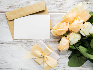 White roses and greeting card on a old wooden table