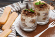 Leinwandbild Motiv Classic tiramisu dessert in a glass on wooden background