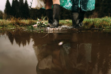 Two Pairs Of Legs Wearing Rubber Boots Go Through The Puddles. From Them Splashes Of Water Fly In The Side Of The Fold