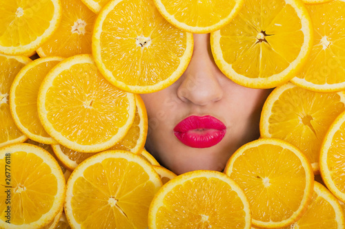 Obraz na plátně  Red lips of a flirtatious young woman among the orange slices covering her face