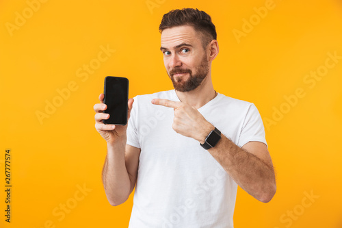 Happy man posing isolated over yellow wall background showing display of mobile phone.
