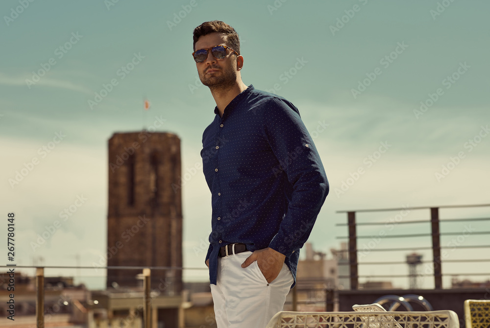 Fototapeta Portrait of handsome man wear sunglasses and standing against the sky