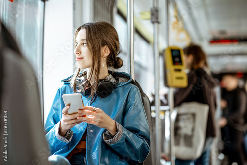 obraz dibond Young stylish woman using public transport, sitting with phone and headphones in the modern tram