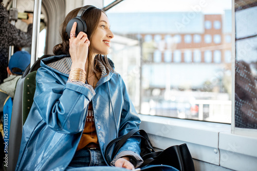 Young woman passenger enjoying trip at the public transport, sitting with headphones near the window in the modern tram - 267781325