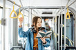 Young woman reading book while standing in the modern tram, happy passenger moving by comfortable public transport