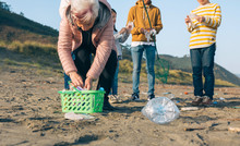 Group Of Volunteers Preparing To Clean The Beach