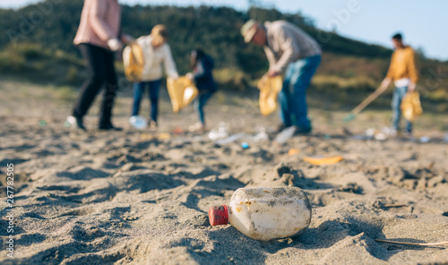 Fotografie, Obraz  Group of volunteers picking up trash on the beach