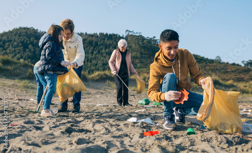 Photo Young man picking up trash with group of volunteers on the beach