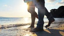 Couple Walk Along Beach, Closeup Of Legs/Bare Feet, Waves Crash At Their Feet