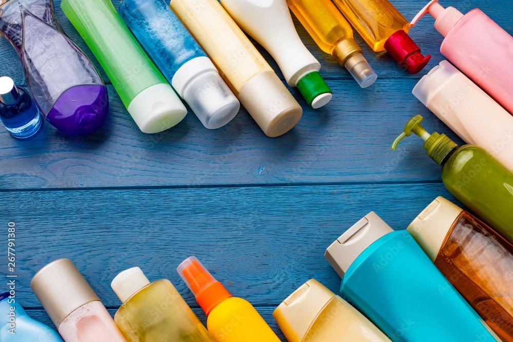 Fototapeta Many kind of shampoo and shower gel bottles and sponge on the table