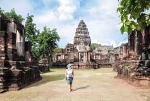 Young Woman Tourist  Enjoying A View Of Old Temple Prasat Hin Phimai, At Phimai Historical Park, Thailand