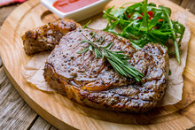 Juicy Ribeye Steak On Wooden Background