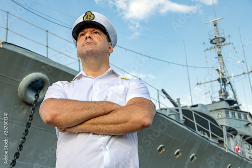 Obraz na plátně Captain standing in dock before warship and  looking ahead