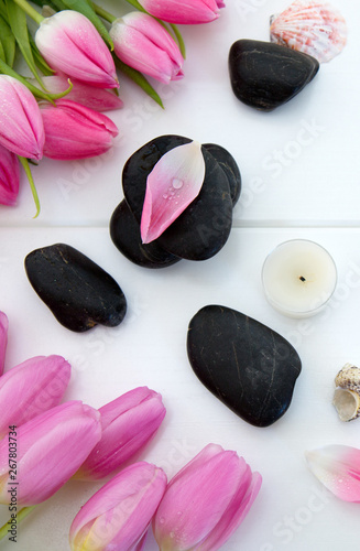 Garden Poster Tulip Spa setting with tulips , black stones and candle on white wood background.