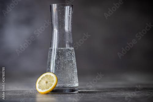 Karafka z woda, ciemne betonowe tło oraz cytryna