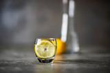 Szklanka z woda oraz cytryną, w oddali dzban z wodą