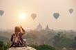 Leinwanddruck Bild Backpacker traveler in Bagan Mandalay Myanmar and sitting watching balloon air in the morning at Bagan.