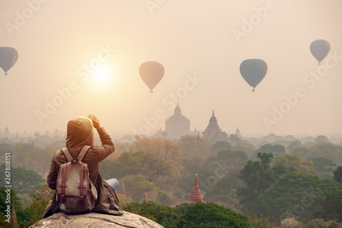 Backpacker traveler in Bagan Mandalay Myanmar and sitting watching balloon air in the morning at Bagan.