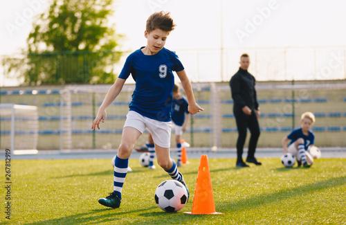 Fotografie, Obraz  Boys training football dribbling in a field