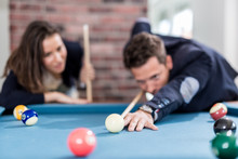 Young Modern Couple Playing Pool Table Billiard Game.