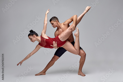 Tableau sur Toile The couple of an athletic modern ballet dancers are posing against a gray studio background