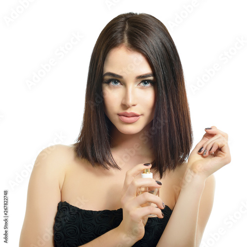 Fototapeta Girl with perfume, young beautiful woman holding bottle of perfume and smelling aroma. Pretty lady posing with a bottle of expensive perfume. obraz