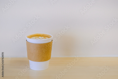 Cafe Close up of paper cup of hot coffee latte with milk foam heart shape art on wooden table.
