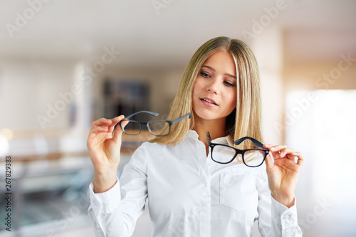 Fototapety, obrazy: Pensive woman with glasses in a business center