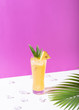 canvas print picture - iced pineapple punch cocktail in glass on color background. summer drink.