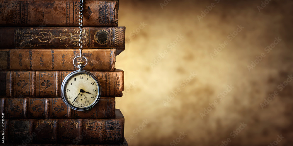 Fototapeta Vintage clock hanging on a chain on the background of old books. Old watch as a symbol of passing time. Concept on the theme of history, nostalgia, old age. Retro style.