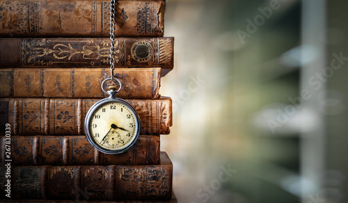 Fototapeta Vintage clock hanging on a chain on the background of old books. Old watch as a symbol of passing time. Concept on the theme of history, nostalgia, old age. Retro style. obraz