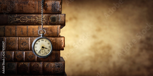 Fotografie, Obraz Vintage clock hanging on a chain on the background of old books