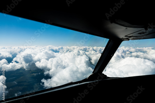 Leinwand Poster Pilots view out of the cockpit window toward clouds and blue sky above