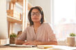 Leinwandbild Motiv Portrait of beautiful mixed race woman looking at camera while sitting at desk in home office lit by sunlight, copy space