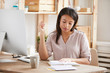 Leinwandbild Motiv Portrait of beautiful Mixed race woman writing in notebook while sitting at desk in office, copy space
