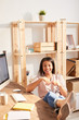 Leinwandbild Motiv High angle portrait of carefree young woman smiling happily while sitting at desk in home office with feet on table, copy space