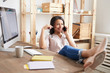 Leinwandbild Motiv Portrait of smiling mixed race woman speaking by phone while sitting at desk in home office with feet on table, copy space