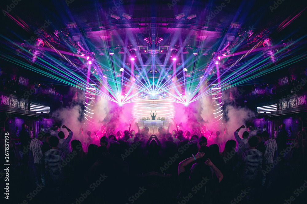 Fototapeta DJ with Hands up in a Nightclub with Lasers