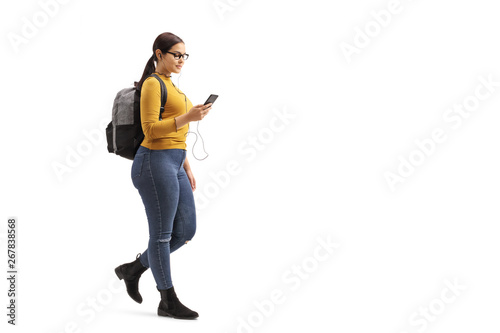 Obraz Female student walking and choosing a song from her mobile phone - fototapety do salonu