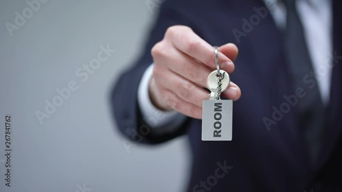 Room word on keychain in male hand rental housing service for business trip