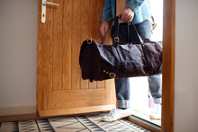 Midsection Of Young Man With Bag Entering Front Door When Coming Back Home.