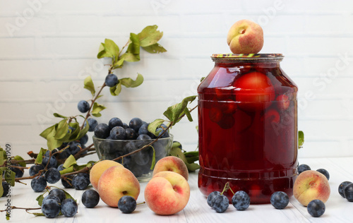 Photo  Compote with peaches and berries of blackthorn in cans are located on a white ba
