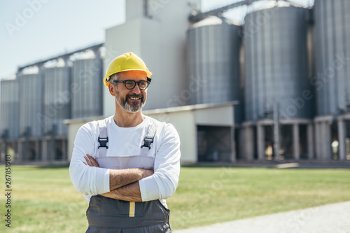 Fototapeta middle aged agricultural worker standing crossed arms in front of grain silo obraz