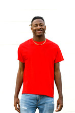 African American Teen Male Wearing A Red T-shirt And Jeans Smiling Against A White Painted Brick Wall