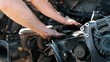 Close-up of auto mechanic hands with a wrench repairing car engine