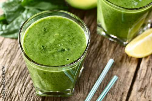 Fresh homemade vegan green smoothie made of spinach, cucumber, avocado and lemon juice (Selective Focus, Focus one third into the drink)