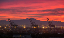 Sunrise Over The Port Of Los Angeles In San Pedro, California, Novermber 2018, With Red Orange Color Of Smoke From Woolsey Fire With Large Giant Cranes And San Bernardino Mountains In Background.